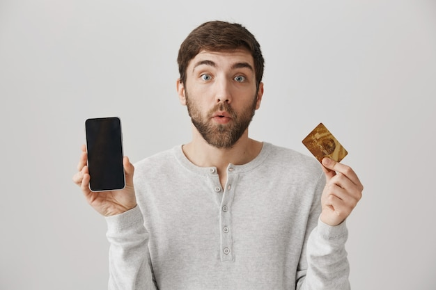 Homme souriant montrant l'écran du smartphone et la carte de crédit. achats en ligne