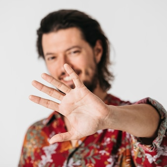 Homme souriant, montrant le geste d'arrêt avec la main, isolé sur fond blanc