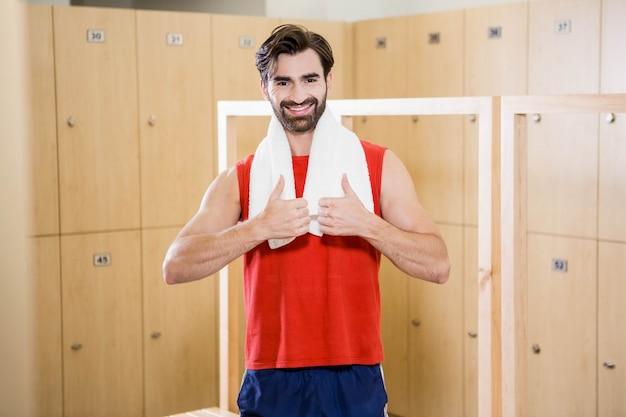 Homme souriant montrant les pouces dans le vestiaire