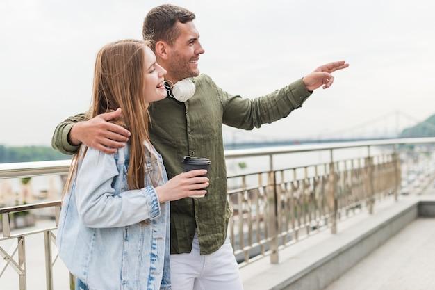 Homme souriant montrant quelque chose à sa petite amie