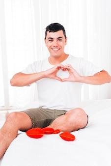 Homme souriant montrant le symbole du coeur
