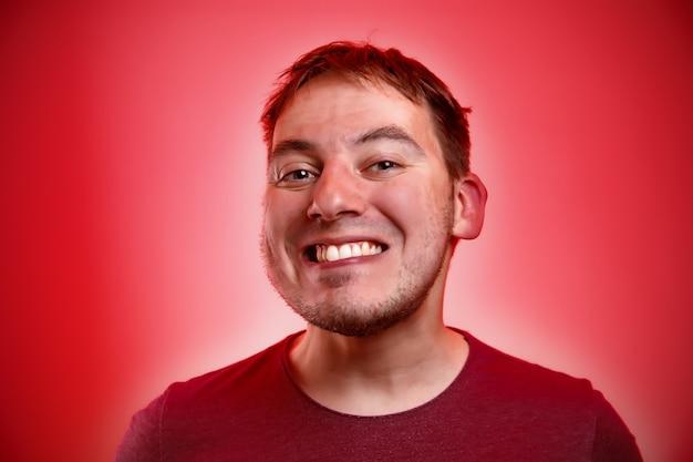 Homme souriant sur un mur rouge.
