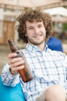 Homme souriant offrant de la bière à la caméra