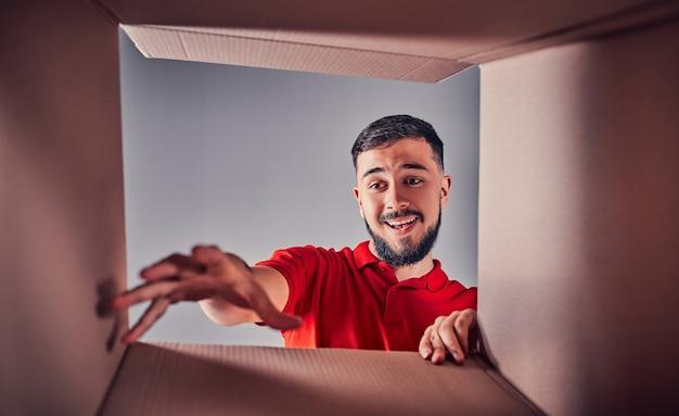 Homme souriant, ouvrant la boîte et regardant à l'intérieur. le concept de colis, livraison, surprise, cadeau et lifestyle