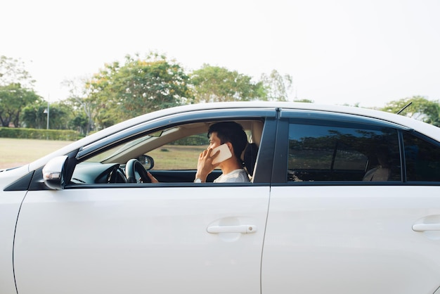Un homme souriant parle sur un téléphone intelligent dans une voiture blanche. l'homme d'affaires a réussi à conduire sa voiture et à parler au téléphone portable.