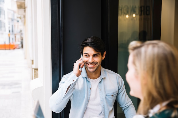 Homme souriant, parler sur smartphone