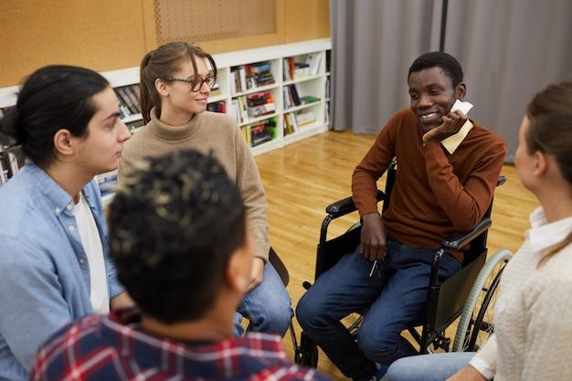 Homme souriant en partage de fauteuil roulant avec un groupe de soutien