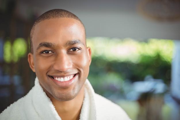 Homme souriant en peignoir buvant du café à la maison