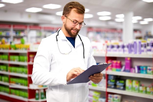 Homme souriant de pharmacien lisant un document dans une tablette numérique
