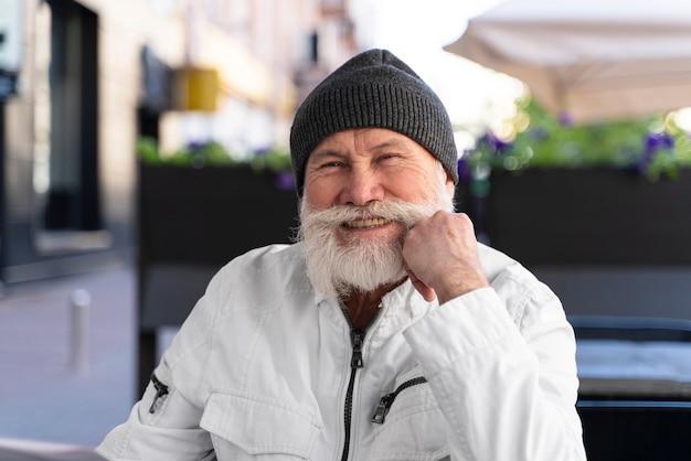 Homme souriant de plan moyen assis sur la terrasse