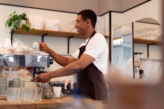 Homme souriant de plan moyen faisant du café
