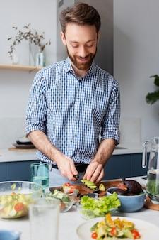 Homme souriant à plan moyen en train de cuisiner