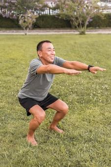 Homme souriant plein coup faisant des squats