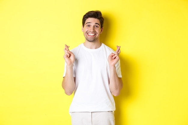 Homme souriant plein d'espoir tenant les doigts croisés, faisant un vœu ou priant, debout sur fond jaune