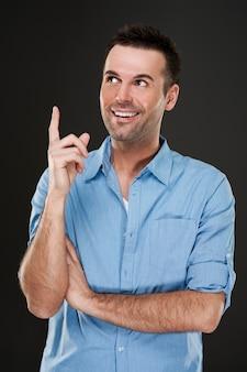 Homme souriant, pointant vers le haut