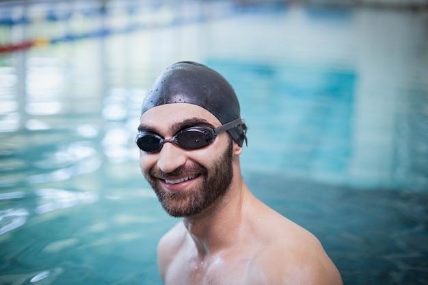 Homme souriant portant bonnet de bain et lunettes à la piscine