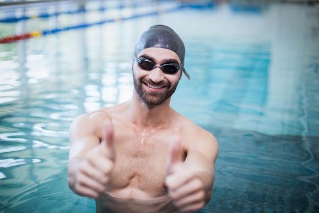 Homme souriant portant bonnet de bain et lunettes de protection avec les pouces vers le haut à la piscine
