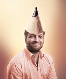 Homme souriant portant une chemise rose avec un cône de crayon sur la tête