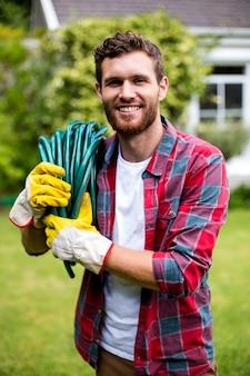 Homme souriant, porter, tuyau jardin, dans, yard