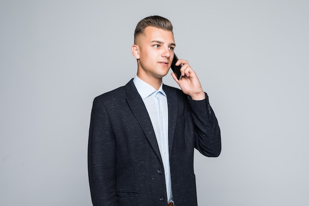 Homme souriant posant avec téléphone portable habillé en veste sombre en studio isolé sur mur gris