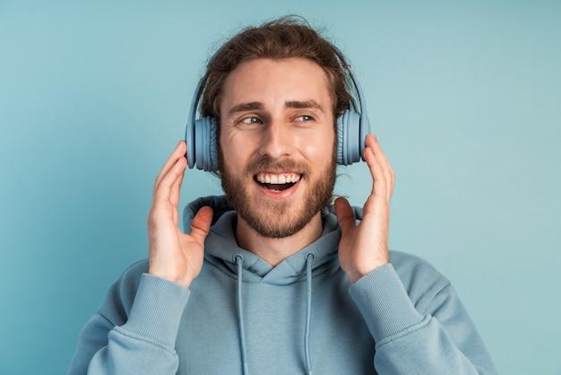 Homme souriant et positif avec une barbe dans les écouteurs écoute de la musique.