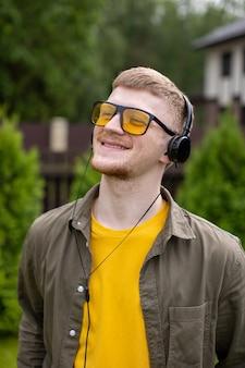 Homme souriant positif dans les écouteurs écouter de la musique d'énergie avec les yeux fermés, nature. liste de lecture de vacances d'été, sons de rêves d'inspiration de voyage de liberté, concept gagnant. copier l'espace de texte