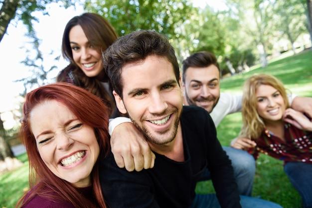 Homme souriant en prenant une auto photo de lui et ses amis avec un parc en arrière-plan