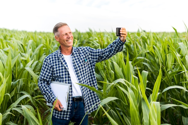 Homme souriant prenant un selfie avec un presse-papier