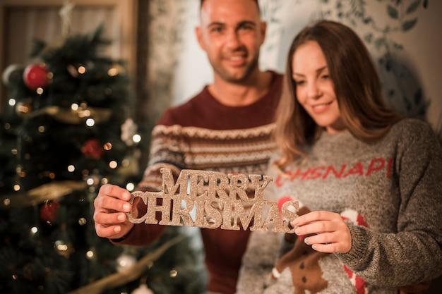 Homme souriant près de femme joyeuse avec tablette de joyeux noël près de sapin décoré