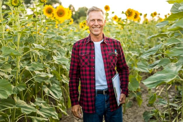Homme souriant avec un presse-papier dans un champ