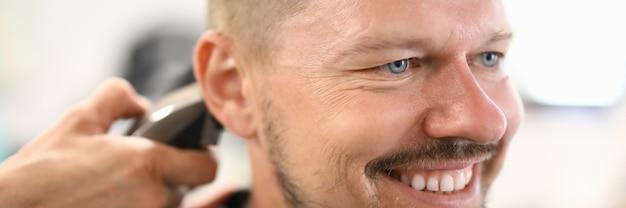 Homme souriant qui a une coupe de cheveux au salon de coiffure.