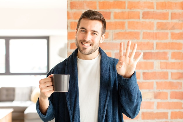 Homme souriant et à la recherche amicale, montrant le numéro quatre ou quatrième avec la main en avant, compte à rebours