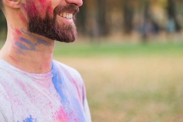 Homme souriant recouvert de peinture multicolore