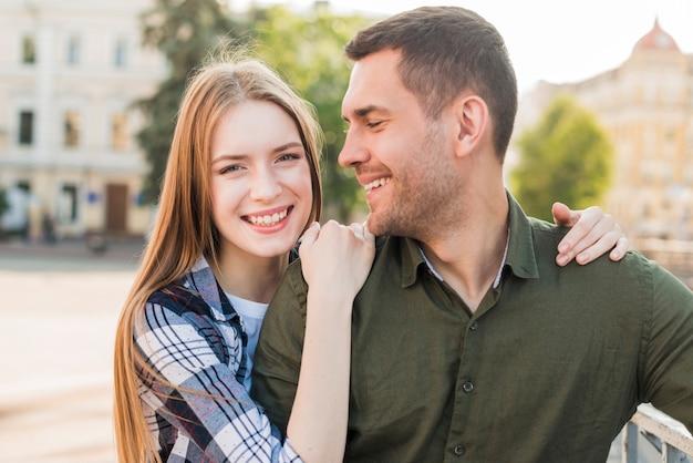 Homme souriant en regardant sa belle petite amie