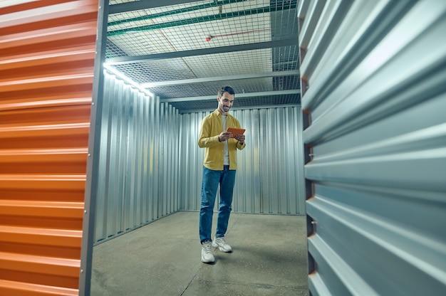 Homme souriant regardant une tablette dans un garage vide