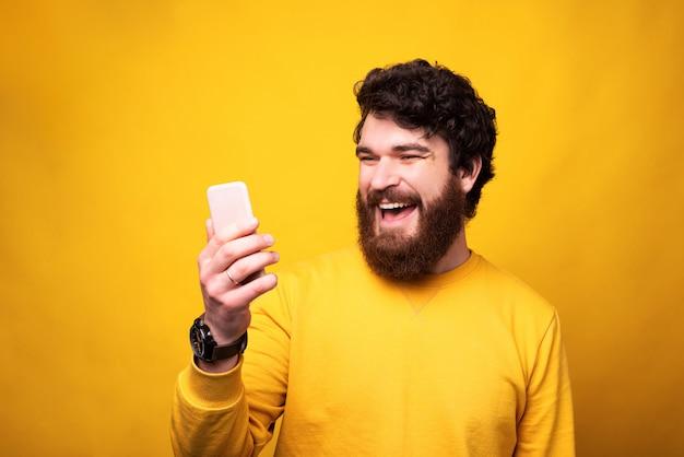 Un homme souriant regarde son téléphone parler en ligne avec ses proches et garder la distance.