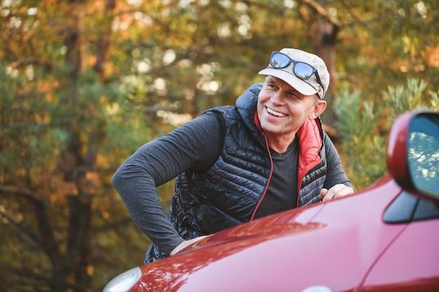 L'homme souriant s'appuie sur le capot d'une voiture rouge