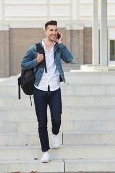 Homme souriant avec un sac à pied et parlant au téléphone portable