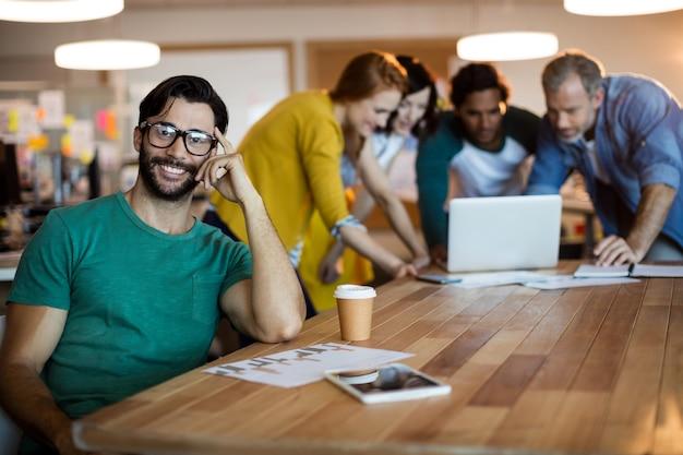 Homme souriant se penchant sur le bureau pendant que l'équipe travaille derrière