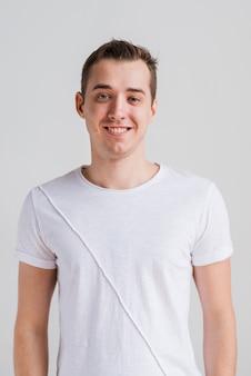 Homme souriant en t-shirt blanc en regardant la caméra
