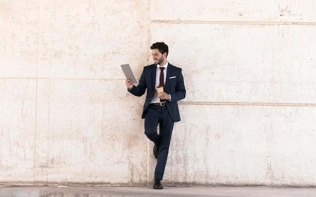 Homme souriant avec tablette et café