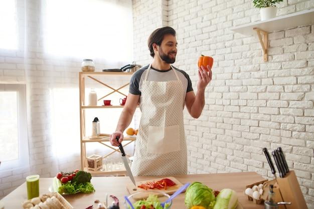 Homme souriant en tablier tranches de poivron orange.