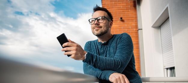 Homme souriant, tapant un message texte