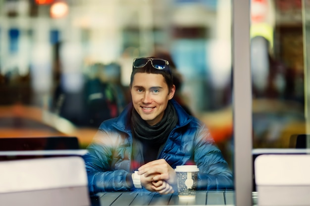 Homme souriant avec une tasse de café dans un café.