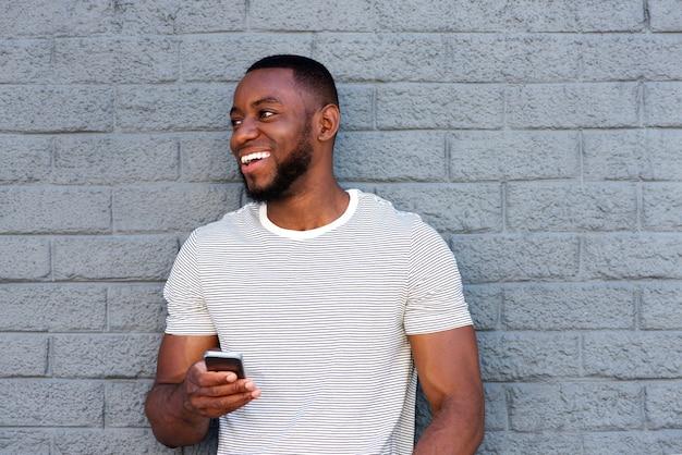 Homme souriant avec un téléphone cellulaire s'appuyant sur un mur gris