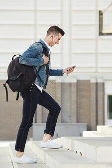 Homme souriant avec un téléphone portable et un casque marchant dans les escaliers