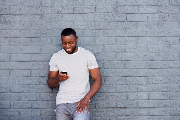 Homme souriant avec téléphone portable s'appuyant sur le mur de briques