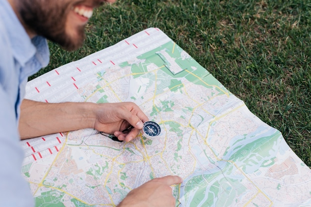 Homme souriant tenant la boussole et pointant vers la carte sur l'herbe