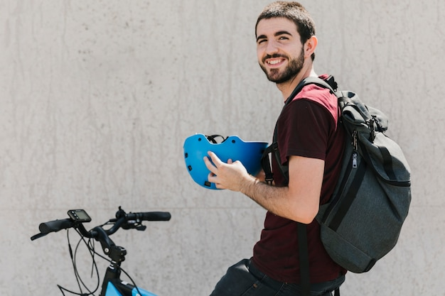 Homme souriant tenant un casque à vélo