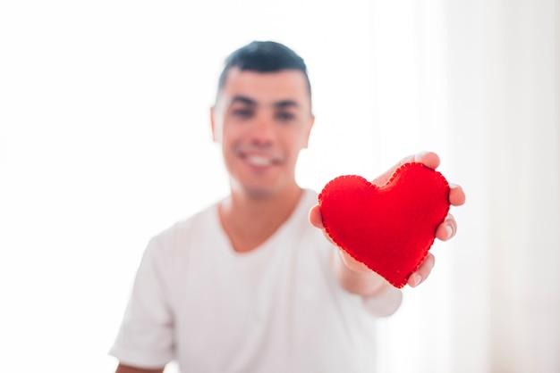 Homme souriant tenant un coeur décoratif